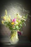 有狂放的领域的水罐开花在土气桌上的束 库存图片