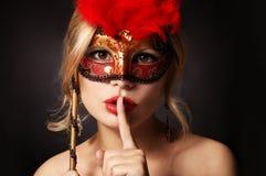 有狂欢节屏蔽的女孩 有手指的妇女在她的显示静寂的红色嘴唇 库存照片