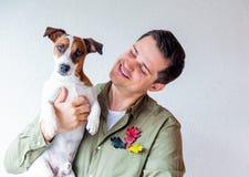 有狗和橡木叶子的英俊的人 库存照片