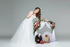 有狗婚礼夫妇的新娘女孩在花下成拱形 库存照片