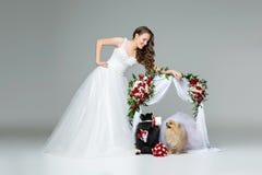 有狗婚礼夫妇的新娘女孩在花下成拱形 图库摄影