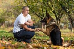 有狗德国牧羊犬的人 库存照片