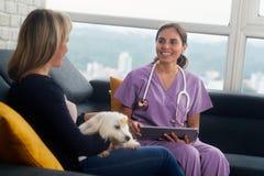有狗所有者和宠物的兽医在家庭参观期间 免版税库存照片