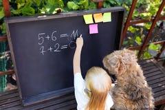 有狗文字答复的逗人喜爱的小女孩对使用白垩的锻炼在黑板 免版税库存照片