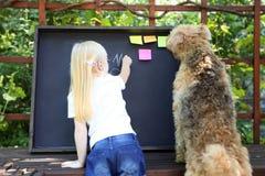 有狗文字答复的逗人喜爱的小女孩对使用白垩的锻炼在黑板 免版税库存图片