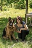 有狗的一个微笑的女孩 免版税库存照片