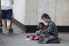 有狗的一个贫困者乞求在街道上 免版税库存图片