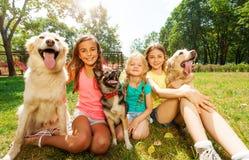 有狗的三个女孩坐草外面 免版税图库摄影