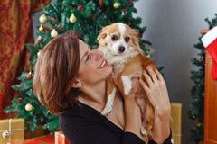 有狗的中年妇女在有圣诞节装饰的屋子里 免版税库存照片