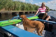 有狗的人在小船 库存照片