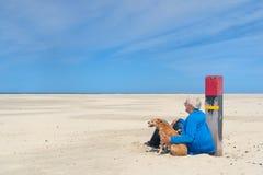 有狗的人在海滩 免版税库存图片