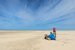 有狗的人在海滩 免版税库存照片
