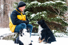 有狗的人在雪 库存图片