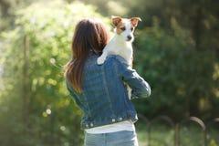 有狗的女孩在她的胳膊 一条小的杰克罗素狗 免版税库存照片