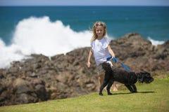 有狗的女孩在海洋 库存照片