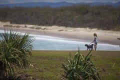 有狗的女孩在海洋 免版税图库摄影