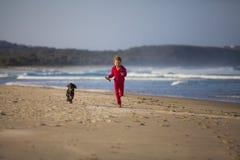 有狗的女孩在海滩 免版税库存照片