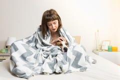 有狗的女孩在温暖的毯子在床上 免版税库存照片