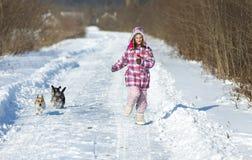 有狗的女孩在雪 库存照片