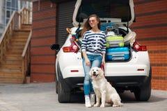 有狗的妇女乘充分汽车手提箱 免版税图库摄影