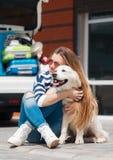 有狗的妇女乘充分汽车手提箱 库存照片