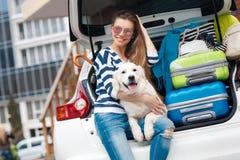 有狗的妇女乘充分汽车手提箱 免版税库存照片
