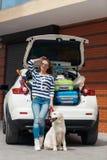 有狗的妇女乘充分汽车手提箱 免版税库存图片