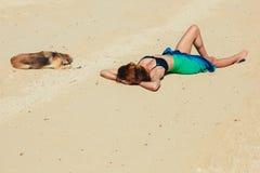 有狗的妇女佩带的布裙在热带海滩 库存图片