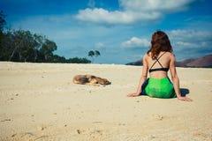 有狗的妇女佩带的布裙在热带海滩 免版税图库摄影