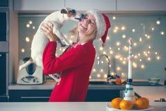 有狗的妇女在圣诞节帽子 图库摄影