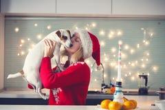 有狗的妇女在圣诞节帽子 库存图片
