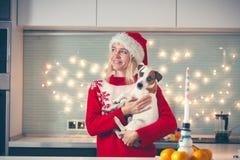 有狗的妇女在圣诞节帽子 免版税库存照片