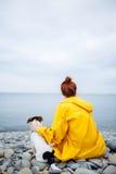 有狗的妇女在海岸 免版税库存图片