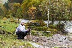 有狗的妇女在阿尔泰山河附近 库存照片