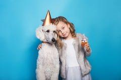 有狗的小美丽的女孩庆祝生日 友谊 爱 结块蜡烛 在蓝色背景的演播室画象 免版税库存照片