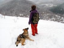 有狗的少妇在多雪的小山顶部 免版税库存照片