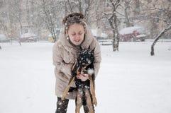 有狗的微笑的女孩在冬天雪 库存照片