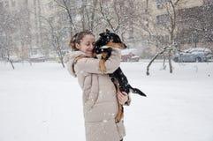 有狗的微笑的女孩在冬天雪 免版税库存照片
