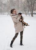 有狗的微笑的女孩在冬天雪 免版税图库摄影