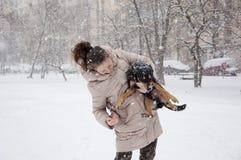 有狗的微笑的女孩在冬天雪 图库摄影