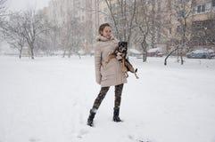 有狗的微笑的女孩在冬天雪 免版税库存图片