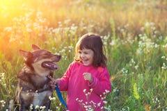 有狗的愉快的小女孩 库存图片