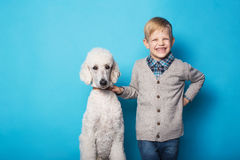 有狗的时兴的男孩 友谊 宠物 在蓝色背景的演播室画象 免版税库存照片
