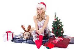 有狗的美丽的十几岁的女孩在驯鹿垫铁和圣诞节 免版税图库摄影