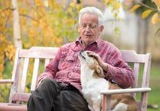 有狗的老人在长凳在公园 库存照片