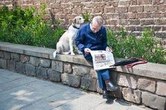 有狗的肩膀的人读一张报纸 免版税库存图片