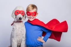 有狗的英俊的矮小的超人 超级英雄 万圣节 在白色背景的演播室画象 库存照片