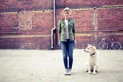 有狗的行家妇女和葡萄酒路在城市骑自行车 图库摄影