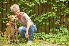 有狗的年长妇女在庭院里 免版税库存图片