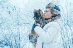 有狗的Pekingese妇女在冬天公园 免版税库存图片